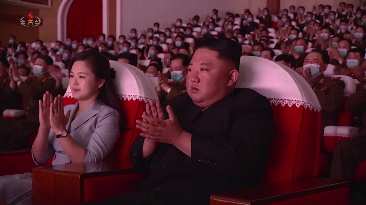 North Korean leader Kim Jong-un (R) and his wife, Ri Sol-ju, applaud as they attend a performance given by the art groups of servicemen's families from large combined units of the Korean People's Army at the Mansudae Art Theatre in Pyongyang on May 5, 2021, in this photo captured from the North's Korean Central Television the next day. (North's Korean Central Television)