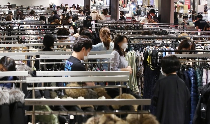 Shoppers look at racks of clothes at a department store in Seoul. (Yonhap)