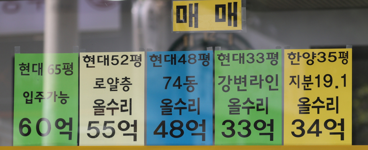 Advertisements on the window of a real estate agency in Apgujeong-dong, Seoul, indicate that asking prices of some apartment units in the district hover around 100 million won ($90,000) per 3.3 square meters. (Yonhap)