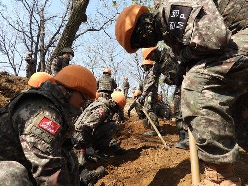 This photo provided by the defense ministry on Tuesday, shows South Korean troops excavating remains and items believed to be from soldiers killed in the 1950-53 Korean War at Arrowhead Ridge in Cheorwon, Gangwon Province. (Ministry of National Defense)