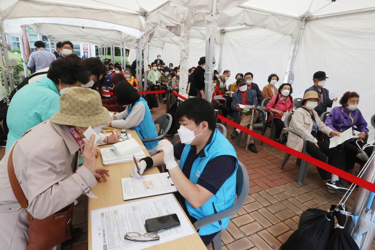 People stand in line to get the Pfizer COVID-19 vaccine at a health clinic in western Seoul on Monday. (Yonhap)