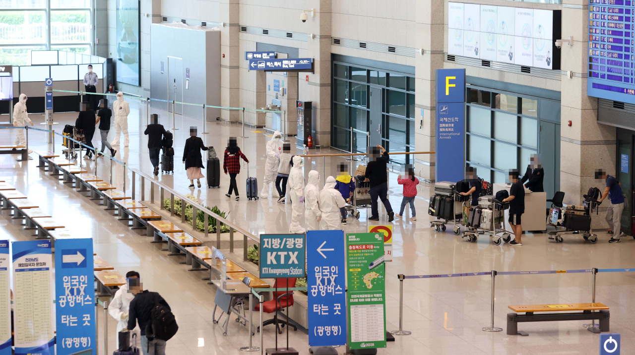 This file photo taken May 12, 2021, shows health workers guiding arrivals from India at Incheon International Airport, west of Seoul. (Yonhap)