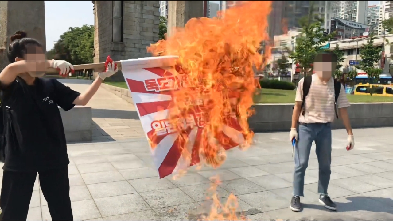 South Korean university students burn the Rising Sun Flag in front of Dongnimmun Gate in Seoul on Wednesday, in this photo captured from the Korean Progressive University Student Union's YouTube channel. (Korean Progressive University Student Union's YouTube channel)