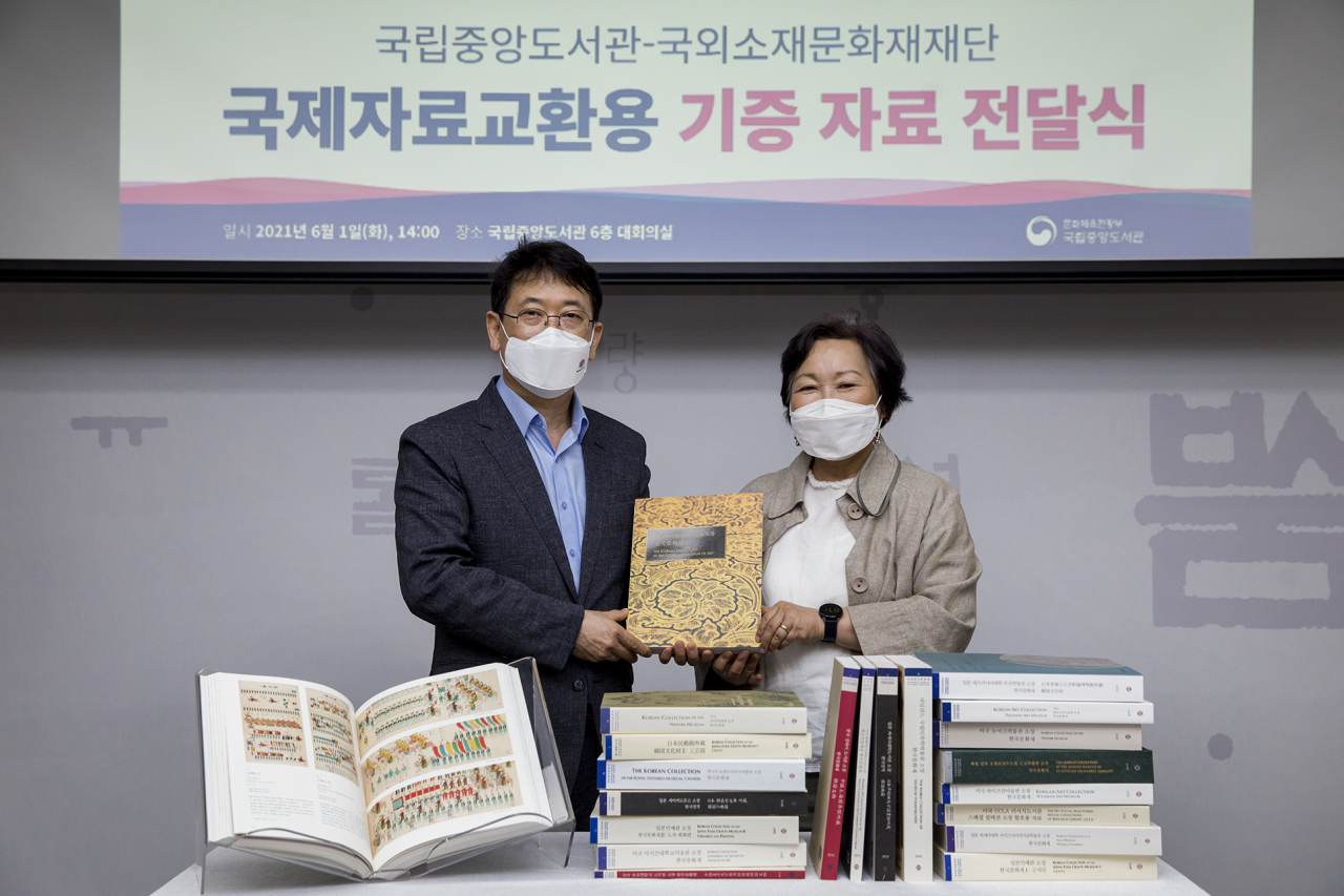 Choi Young-chang (left), chairman of the Korea Cultural Heritage Foundation, and Suh Hye-ran, director of the National Library of Korea, attend a donation ceremony Tuesday.