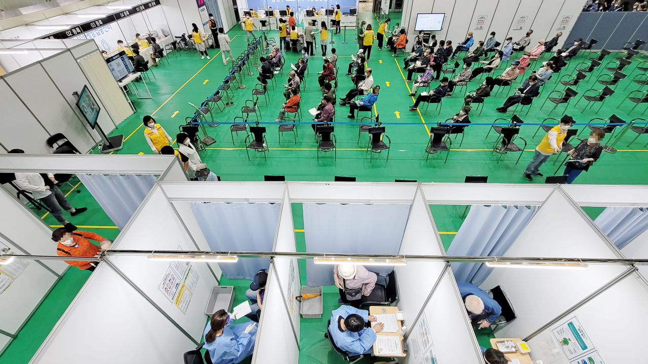 Seoul residents wait in line at a COVID-19 vaccination clinic in Jungnang, a northern district in the city, on Thursday morning. People in their 60s and older are now eligible for vaccination. (Yonhap)