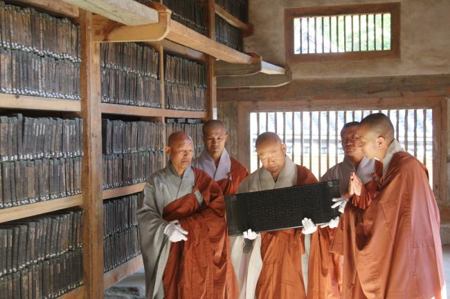 "Ven. Sunhye (center) holds one of the original Tripitaka Koreana, or ""Palmandaejangyeong,"" printing blocks to be shown to the public to commemorate the upcoming 2013 Tripitaka Koreana Festival. (Yonhap)"