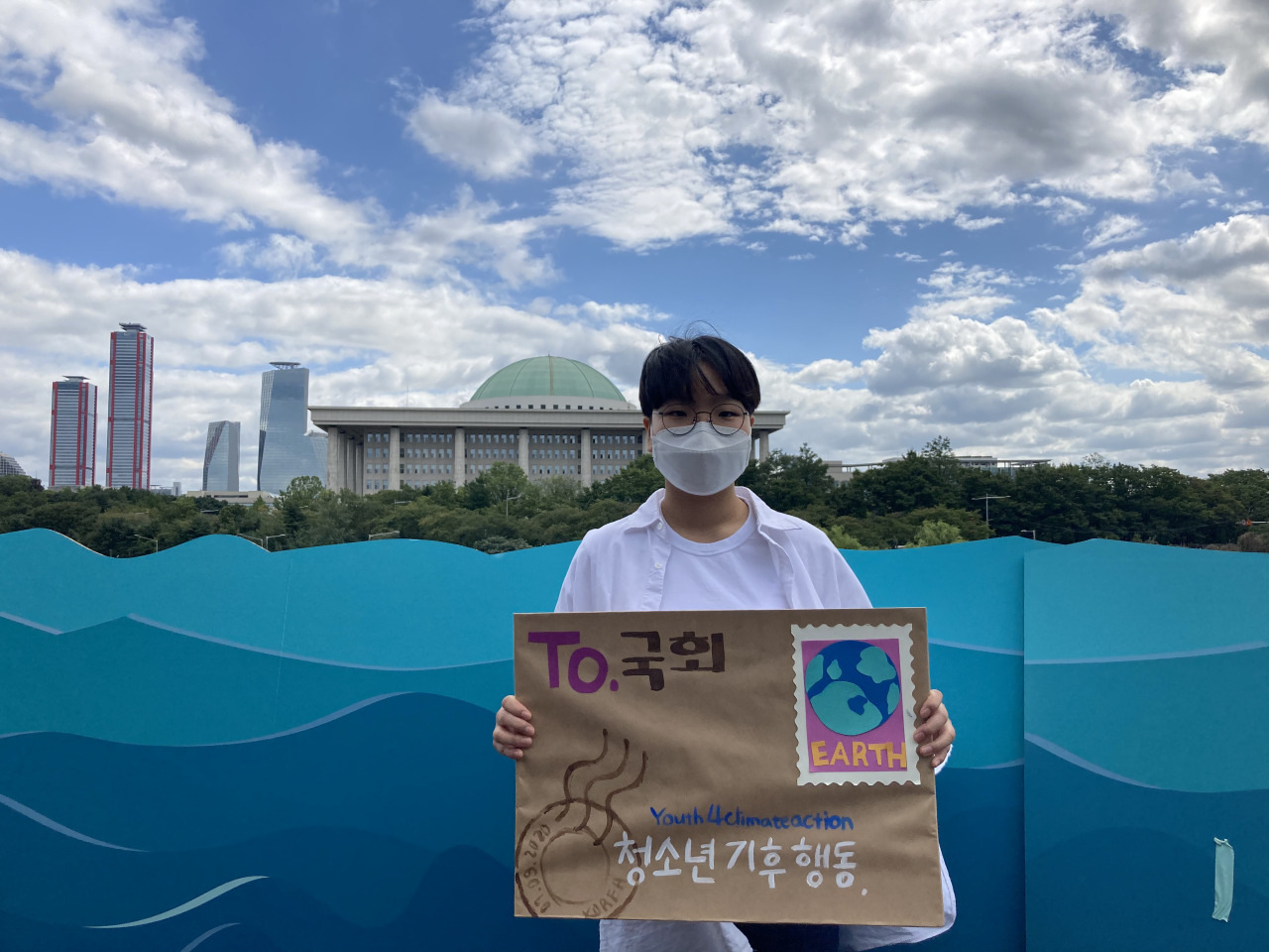 Teenage climate activist Yoon Hyeon-jeong poses for a photo in front of the National Assembly in Seoul while holding a placard urging lawmakers to take action on the climate crisis. (Yoon Hyeon-jeong)