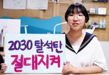 """Teenage climate activist Yoon Hyeon-jeong holds up a placard reading """"2030 coal-free, keep the promise!"""" (Lee Sang-sub/The Herald Business)"""