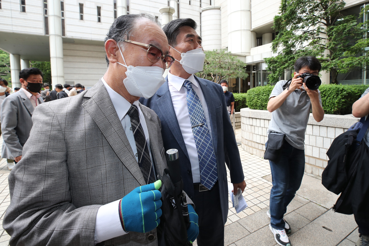 Lim Cheol-ho (left), whose father died in Japan during the war as a victim of forced labor, leaves the court after the judge dismisses the lawsuit filed by 85 plaintiffs on Monday. (Yonhap)