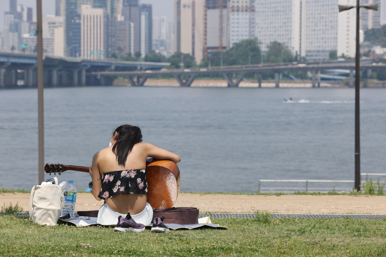 A woman in face mask plays the guitar at a riverside park in Yeouido, central Seoul, on Sunday. (Yonhap)