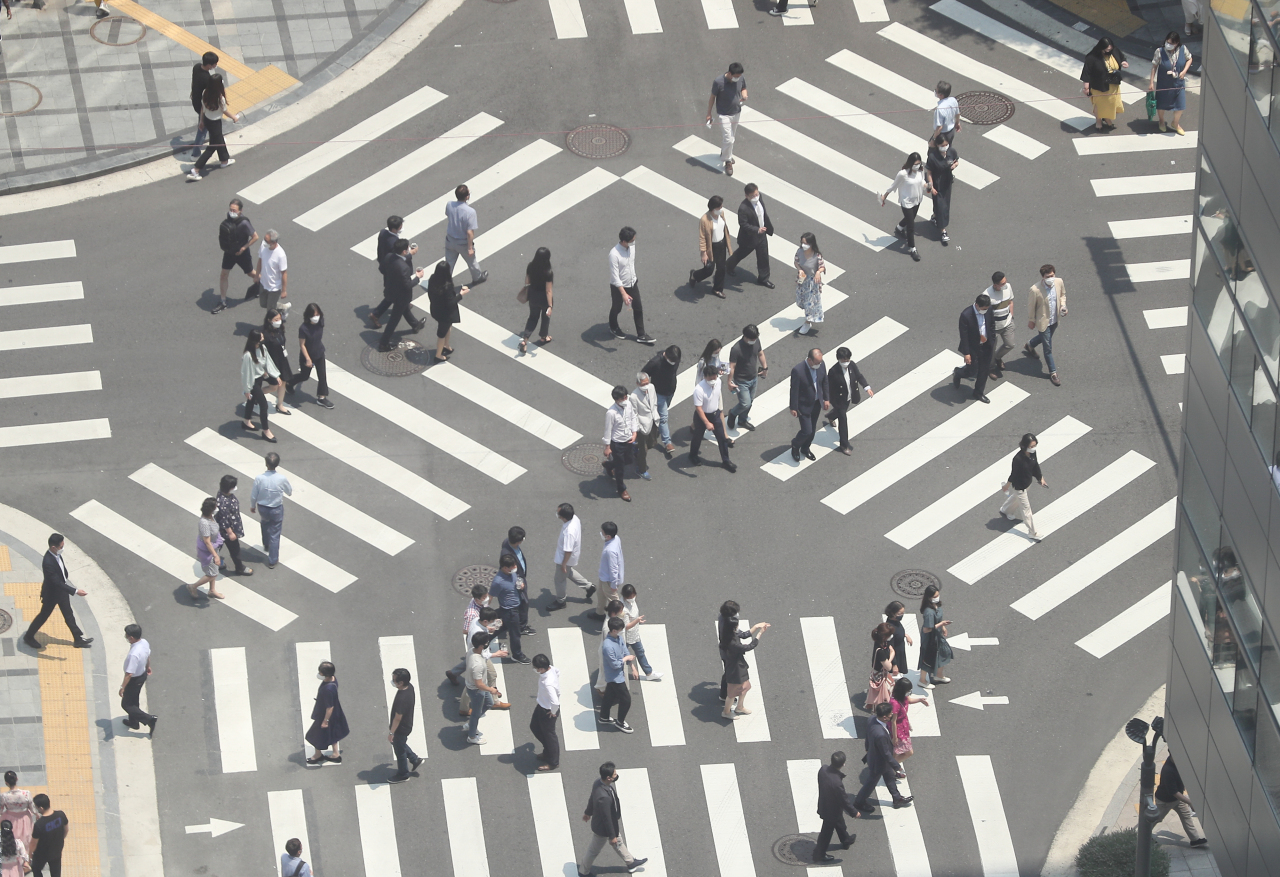 Office workers cross streets near Seoul City Hall during lunch hour on Wednesday. (Yonhap)