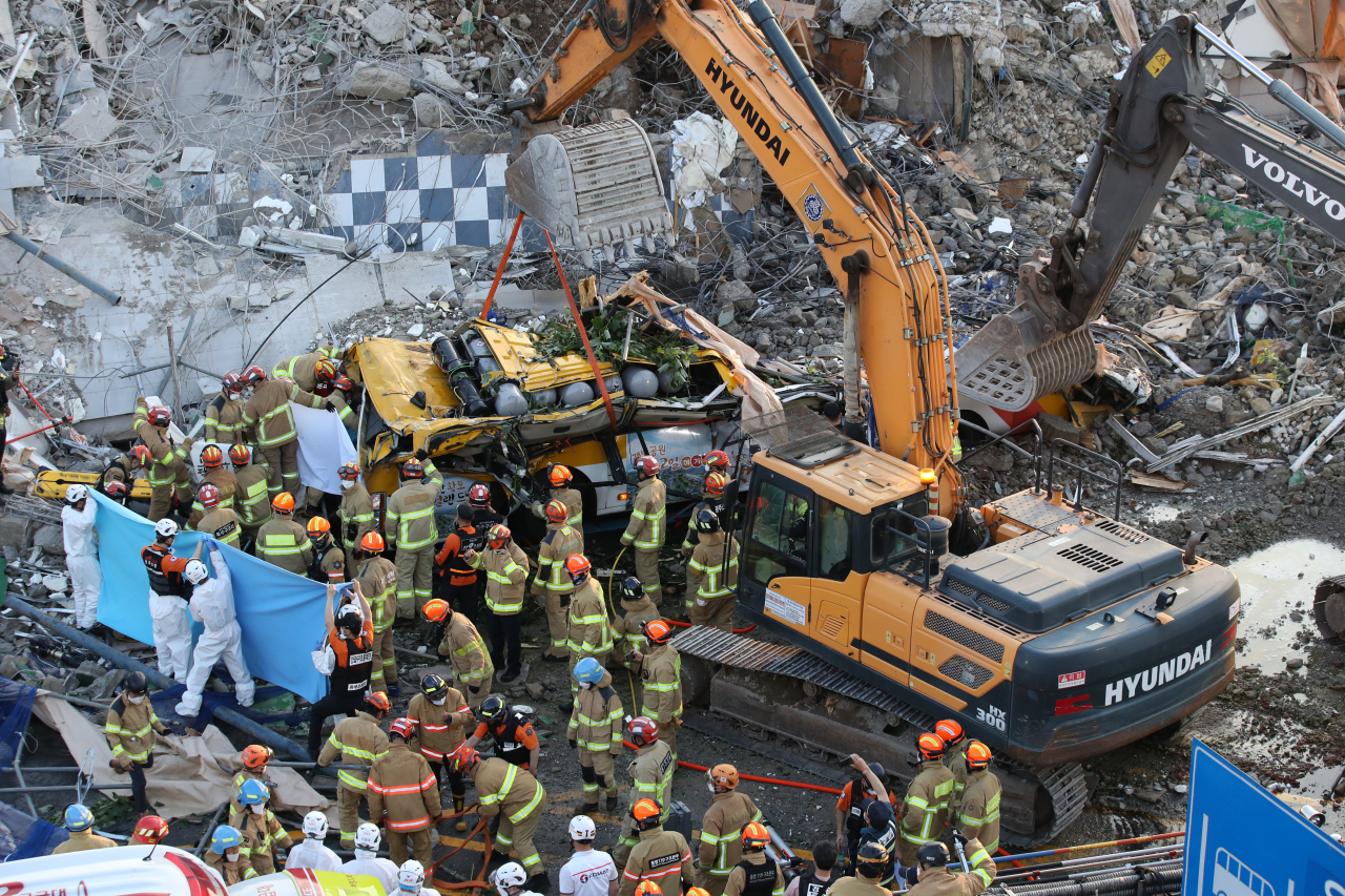 Firefighters rescue people trapped under a mound of debris in the southwestern city of Gwangju on Wednesday. (Yonhap)