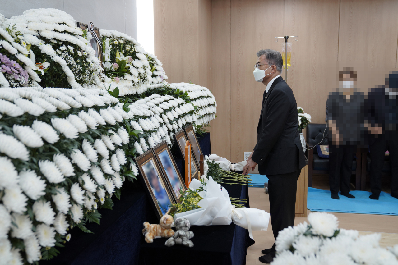 In this photo provided by Cheong Wa Dae, President Moon Jae-in pays silent tribute to a late female Air Force noncommissioned officer at a funeral home of Armed Forces Capital Hospital in Seongnam, just south of Seoul, on Sunday. (Cheong Wa Dae)