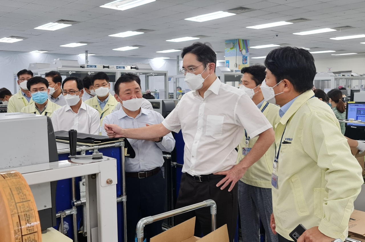 Lee checks out at smartphone products at Samsung's plant in Hanoi, Vietnam in 2020. (Samsung Electronics)