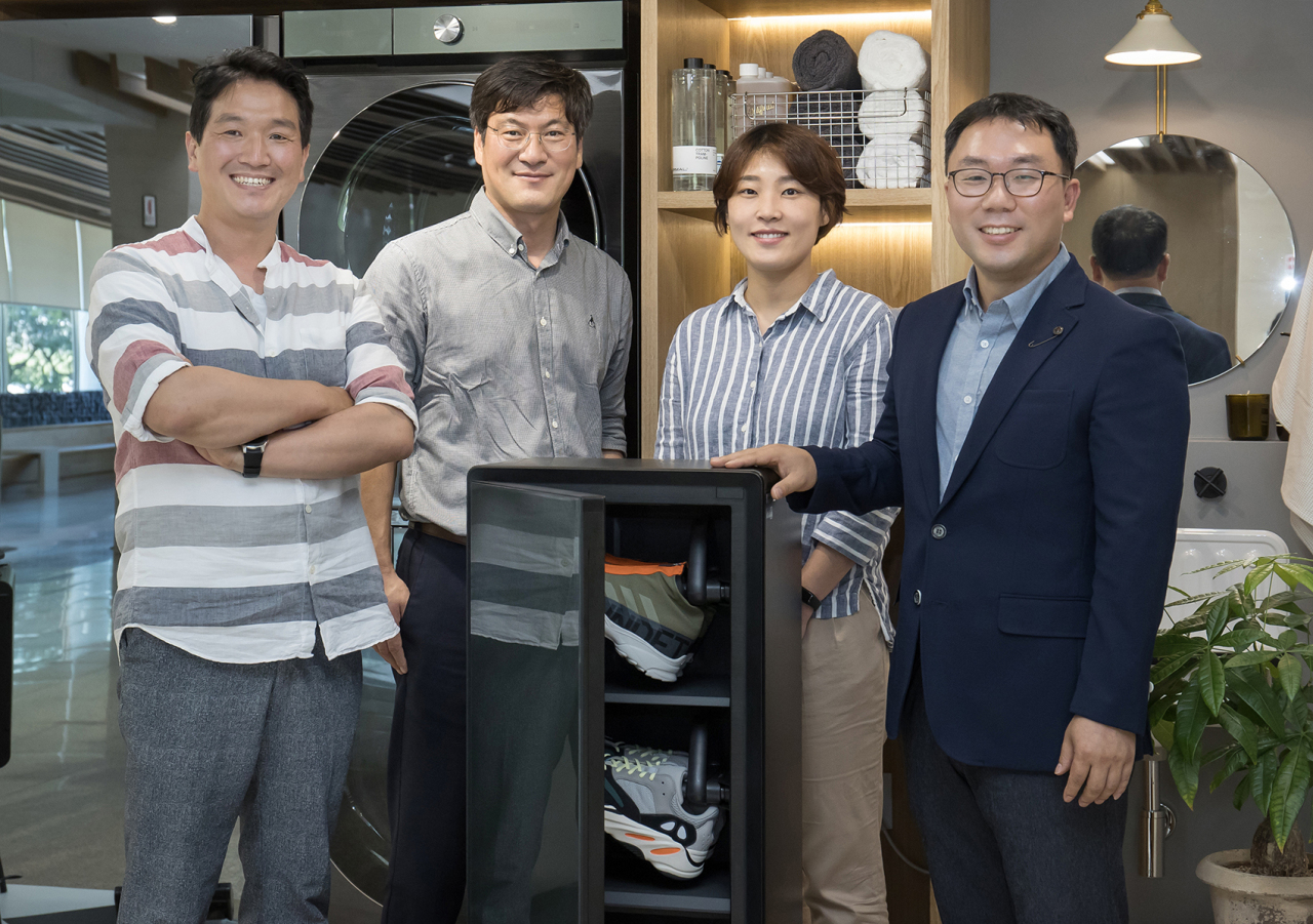 From left: Lee Jung-hee, Ko Young-chul, Kim Myoung-sun and Seo Dong-pil of Samsung Electronics' consumer electronics business pose with a ShoeDresser product exhibited in the lobby of the company headquarters in Suwon, Gyeonggi Province, on June 4. (Samsung Electronics)