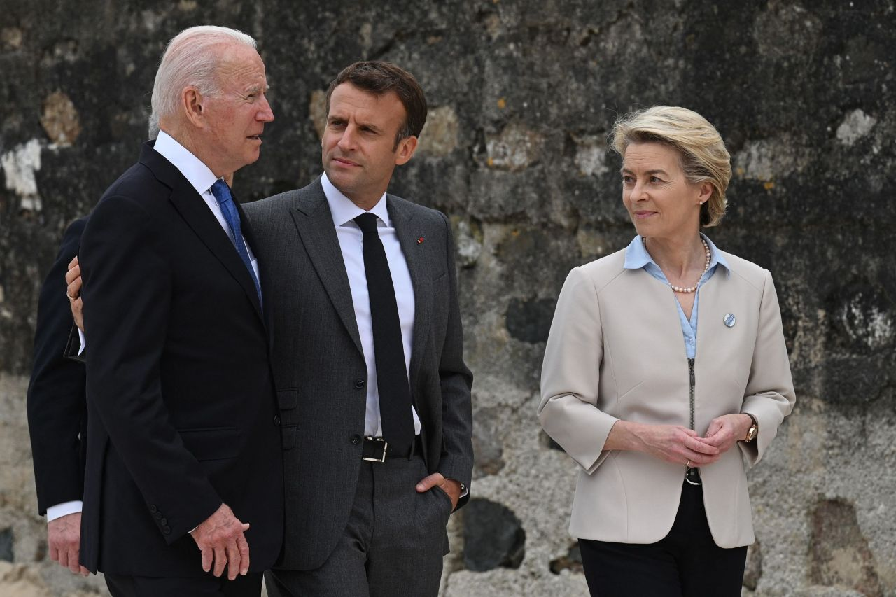US President Joe Biden (L) and France's President Emmanuel Macron (C) speak as President of the European Commission Ursula von der Leyen (R) looks on after the family photo at the start of the G7 summit in Carbis Bay, Cornwall on Friday. (AFP-Yonhap)