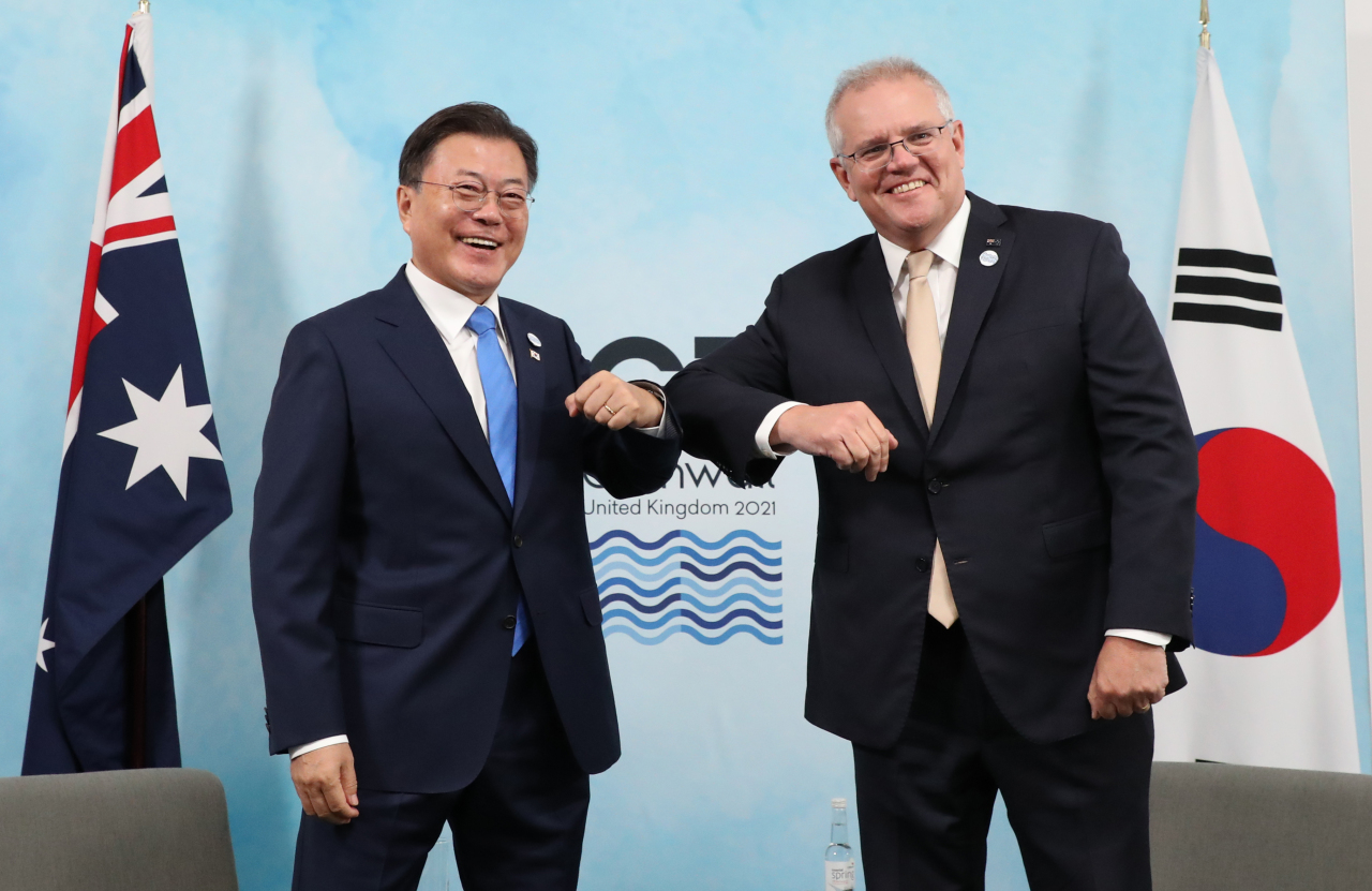 South Korean President Moon Jae-in and Australian Prime Minister Scott Morrison gesture before having summit talks in Britain on Saturday. (Yonhap)