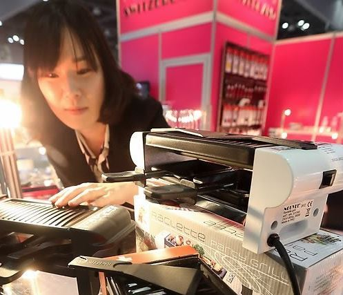 A customer in a store looks at a small electric griddle designed for households consisting of one or two people. (Yonhap)
