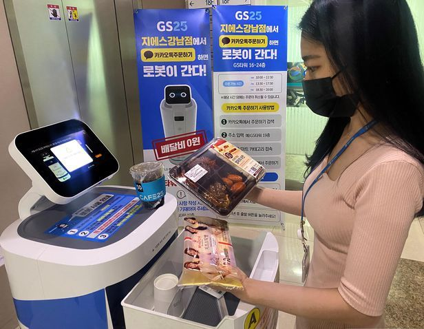 A GS Retail employee receives items ordered through GS25's robot delivery service. (GS Retail)