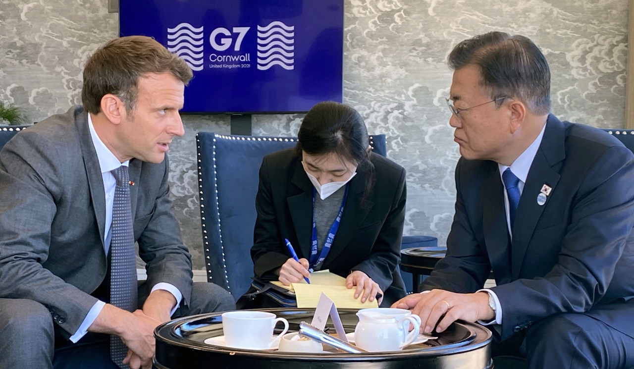 Presidents Moon Jae-in and Emmanuel Macron hold talks on the sidelines of the G-7 summit in Cornwall, England, Sunday. (Yonhap)