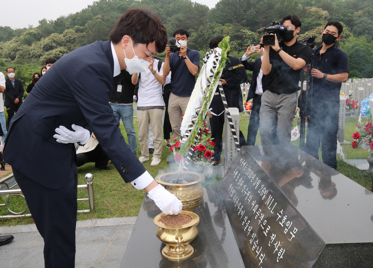 Lee Jun-seok, new chairman of the main opposition People Power Party, burns incense in front of the tombs of South Korean sailors of the sunken naval ship Cheonan during a visit to the National Cemetery in Daejeon, 164 kilometers south of Seoul, on Monday. (Yonhap)