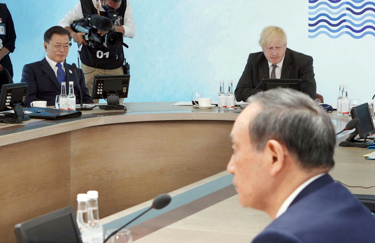 President Moon Jae-in (left), British Prime Minister Boris Johnson (center) and Japanese Prime Minister Yoshihide Suga attend a G-7 session in the seaside resort of Carbis Bay in Cornwall, Britain, on Sunday. (Yonhap)