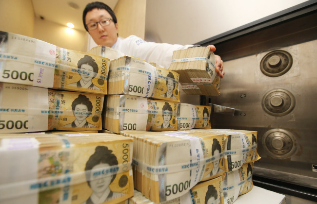 Bundles of 50,000 won banknotes are stacked at a bank in Seoul. (Yonhap)