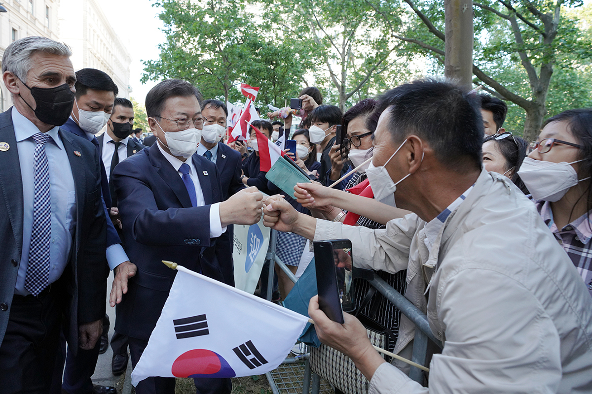 President Moon Jae-in gives a fist bump to a Korean resident in Austria upon his arrival in Vienna on Sunday. (Cheong Wa Dae)