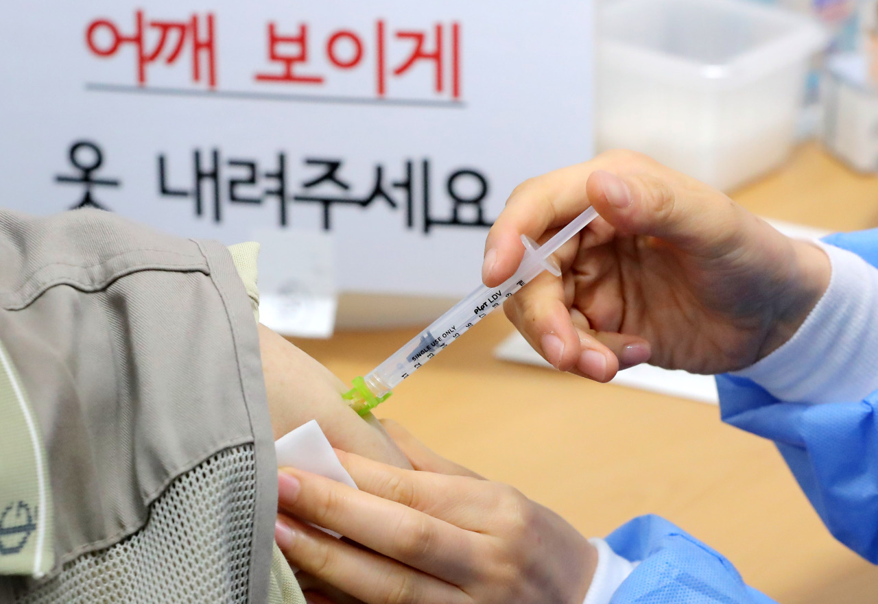 A health worker gives a COVID-19 vaccine shot at an inoculation center in Seoul on Saturday.