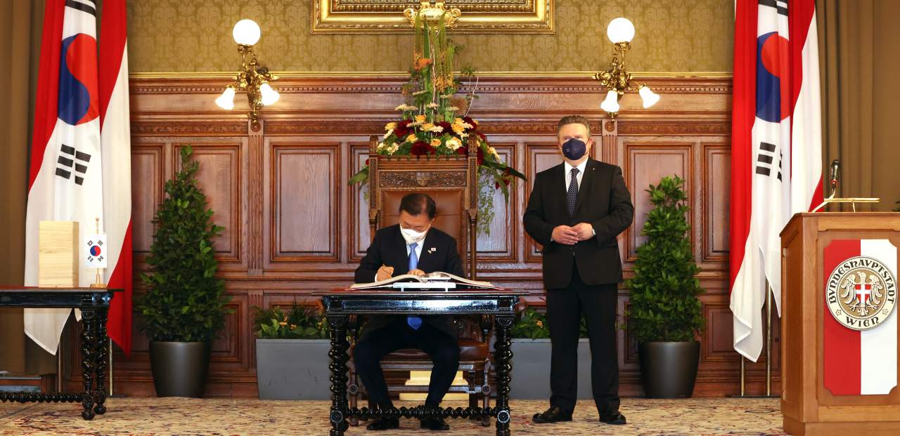 South Korean President Moon Jae-in signs a guest book during a visit to the Vienna City Hall for a meeting with Mayor Michael Ludwig on Monday. (Yonhap)