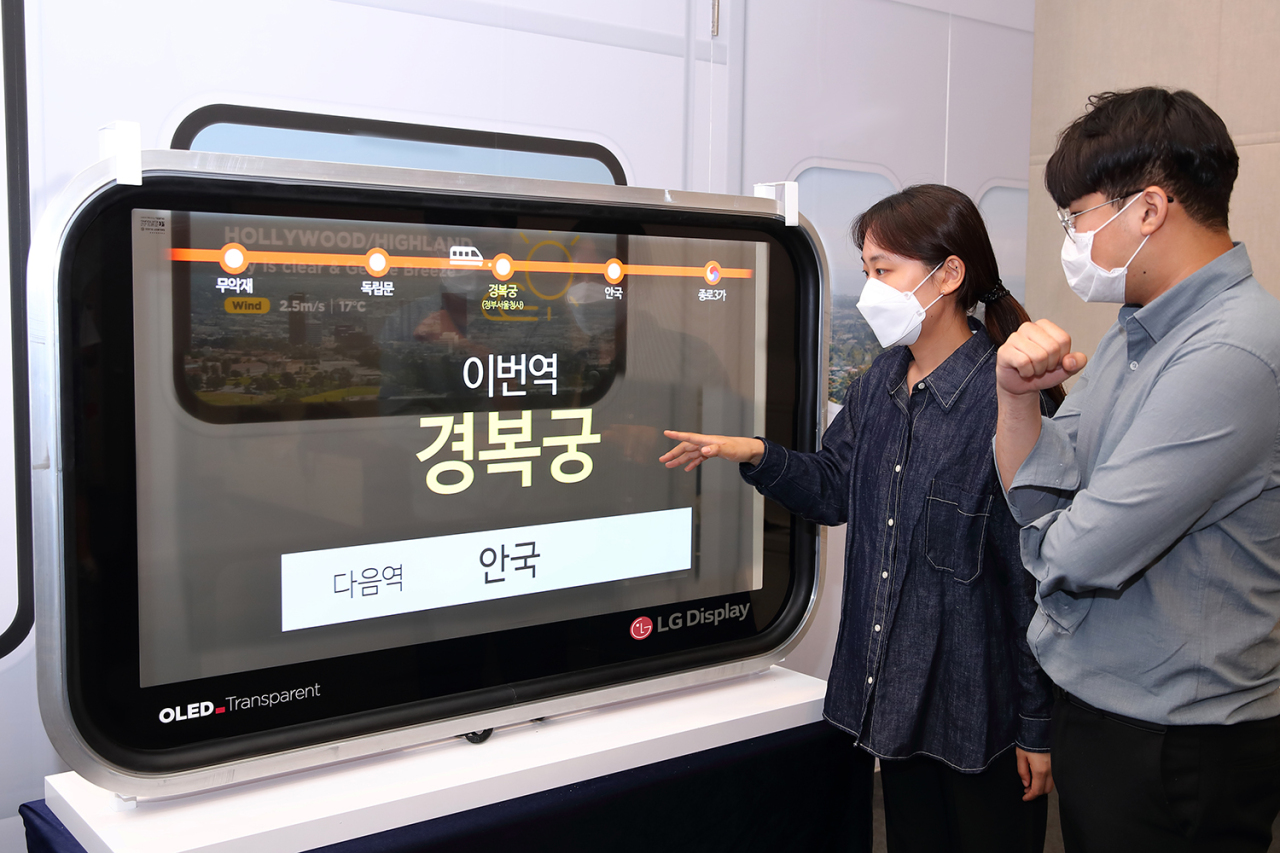 Visitors look at a transparent OLED panel that displays the name of a subway station at Korea Railways & Logistics Fair 2021 being held in Busan on Wednesday. (LG Display)