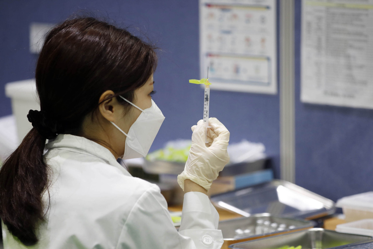 A medical worker prepares to administer a shot at a public COVID-19 vaccination center. (Yonhap)