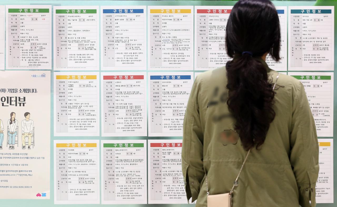 This file photo shows a woman looking at job advertisements. (Yonhap)