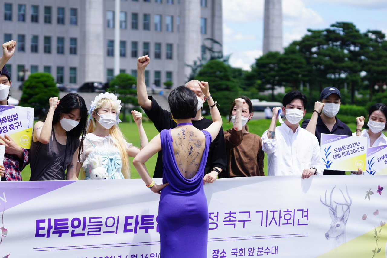 """Rep. Ryu Ho-jeong (center) of the minor Justice Party shouts out slogans during a press conference held at the National Assembly to demand changes to """"outdated"""" laws on tattoos. Ryu wore a purple backless dress to show off her temporary body art as a means to show her support for tattooing as an acceptable form of expression. (Office of Rep. Ryu Ho-jeong/Yonhap)"""