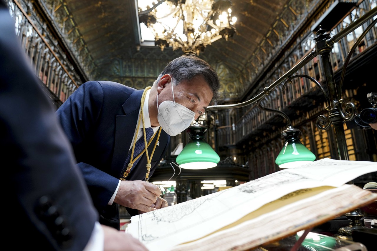 """President Moon Jae-in looks at the """"Map of Joseon Kingdom"""" at the Spanish Senate Library in Madrid on Wednesday. (Yonhap)"""