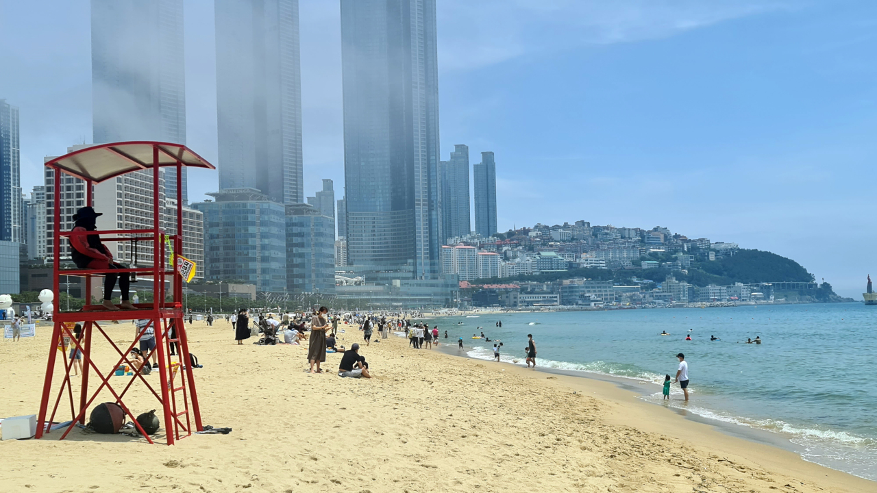 People in face masks are seen at a beach in Haeundae, Busan, on Sunday. (Yonhap)