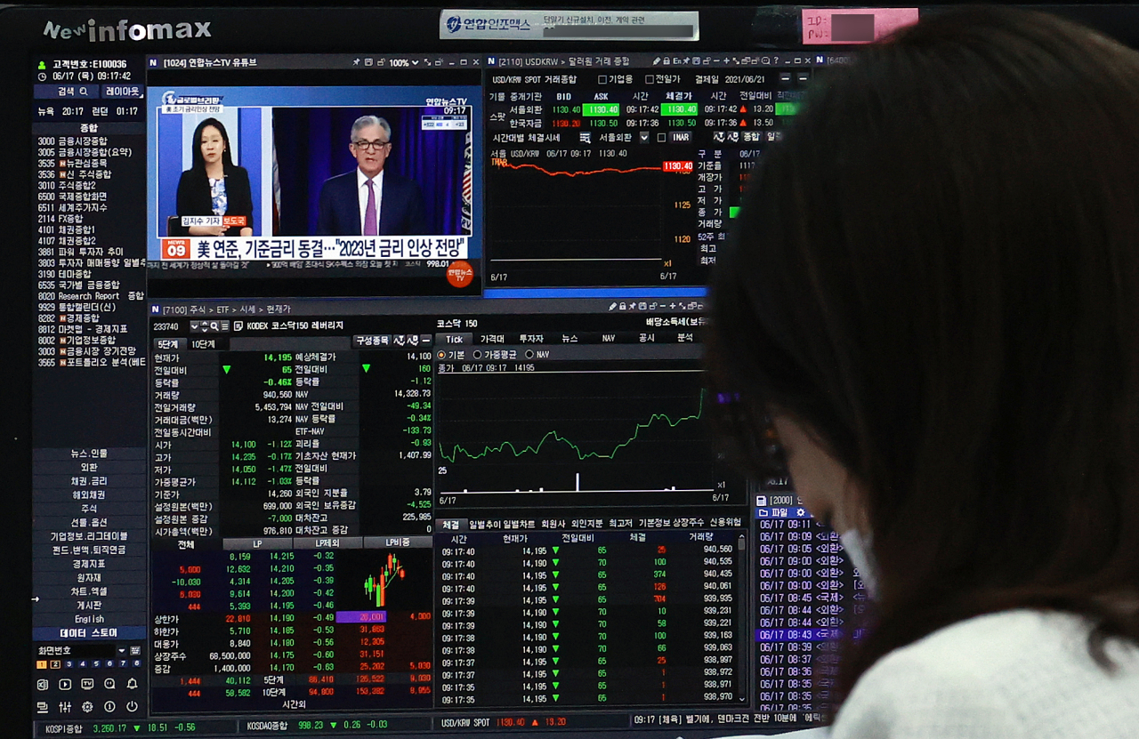A Hana Bank dealer watches TV reports on the US Fed's projection of rate hike in 2023 on Thursday morning. (Yonhap)