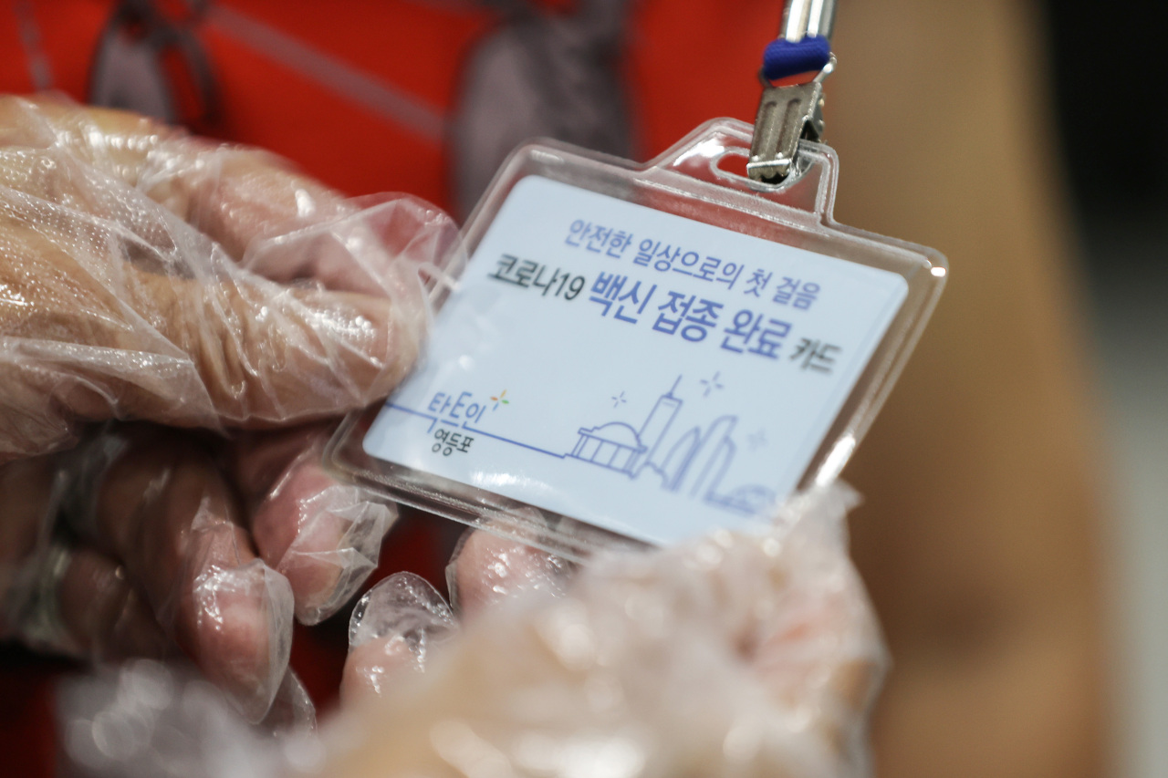 An elderly person, who just completed his COVID-19 vaccination, looks at his vaccine card at a vaccination center in southwestern Seoul on Thursday. (Yonhap)