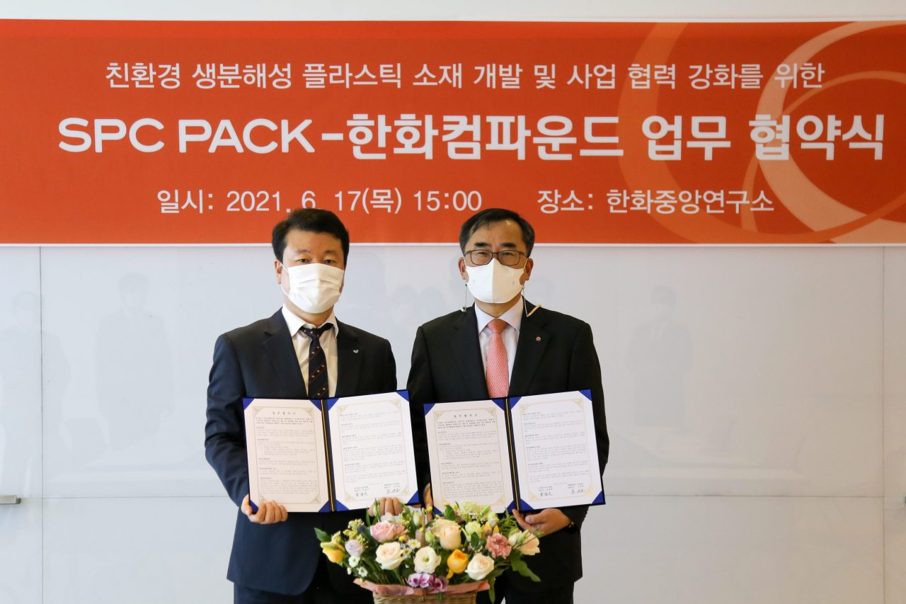 Hanwha Compound CEO Oh Sae-won (right) and SPC Pack CEO Kim Chang-dae sign an agreement to co-develop biodegrable plastic packing material at Hanwha Solutions Chemical Division Research and Development center on Thursday. (Hanwha Solutions)