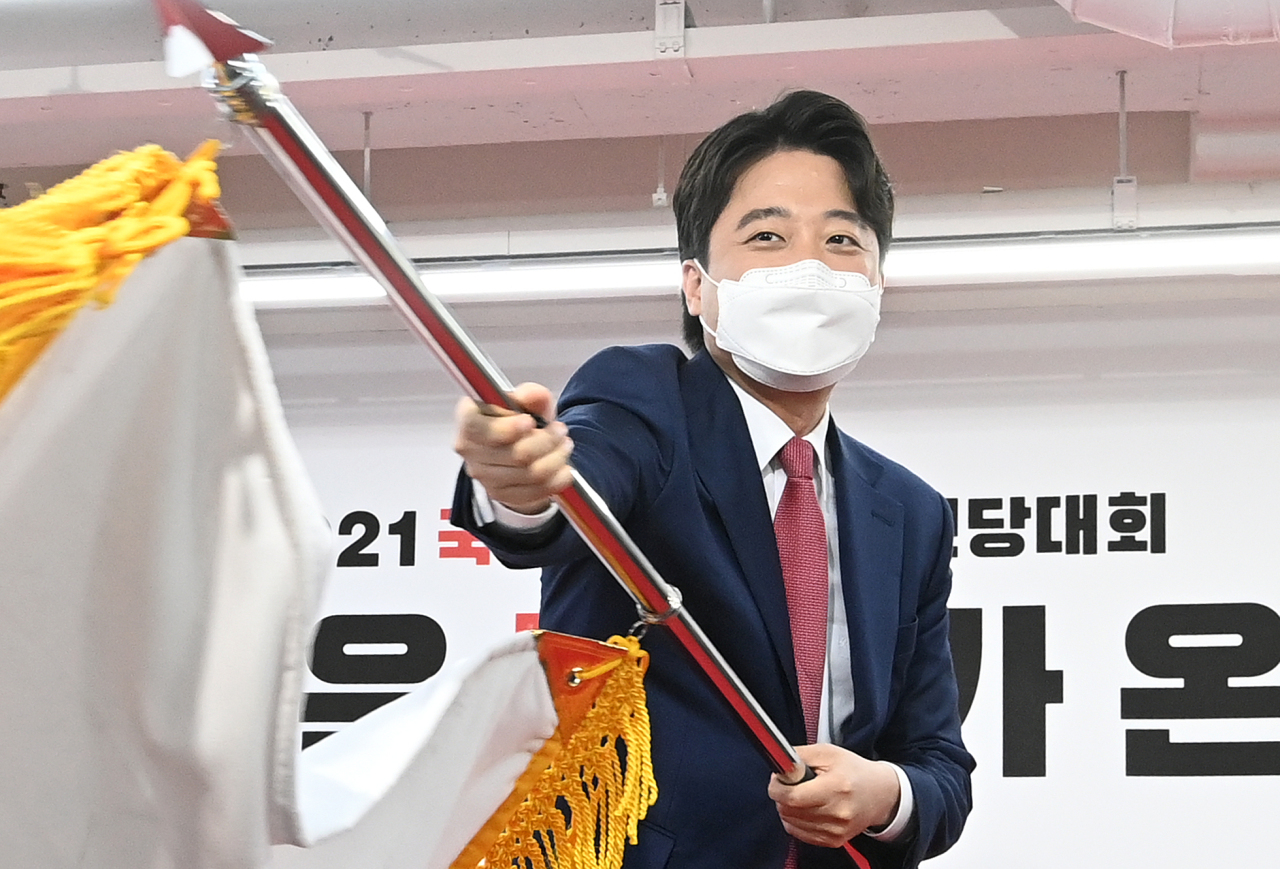 Lee Jun-seok, 36, waves the flag of the main opposition People Power Party after being elected as its chairman at the party's national convention in Seoul on June 11, 2021. He became the youngest-ever leader in the history of the country's main political parties. (Yonhap)