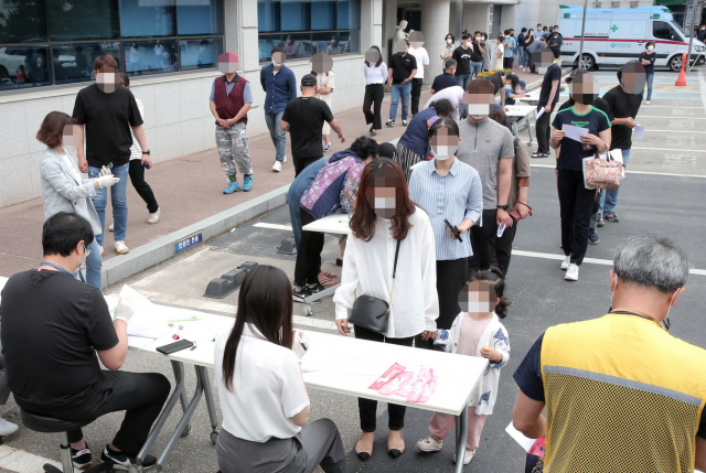 Citizens wait in line to receive new coronavirus tests at a temporary testing site in Yanggu, Gangwon Province on Thursday. (Yonhap)