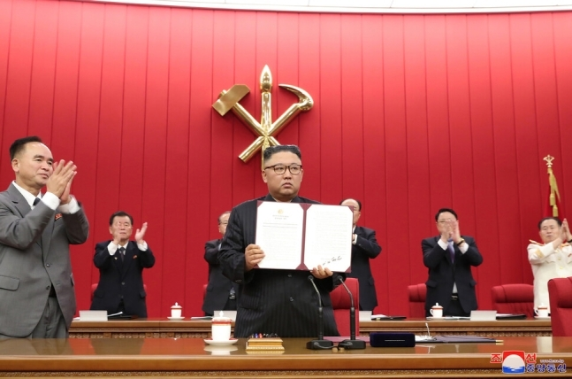 North Korean leader Kim Jong-un holds up a document carrying his signature at the third plenary meeting of the eighth Central Committee of North Korea's Workers' Party on its third-day schedule in Pyongyang on Thursday, to discuss international affairs, including the Biden administration's North Korea policy, in this photo provided by the Korean Central News Agency. (Yonhap)