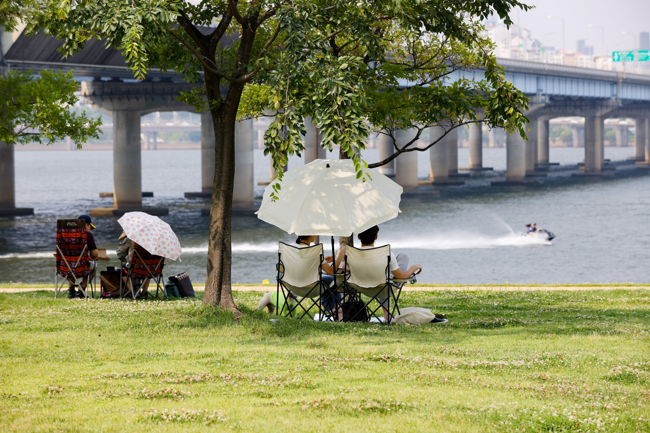 People enjoy the sun at a park in Yeouido, central Seoul, on Sunday. (Yonhap)