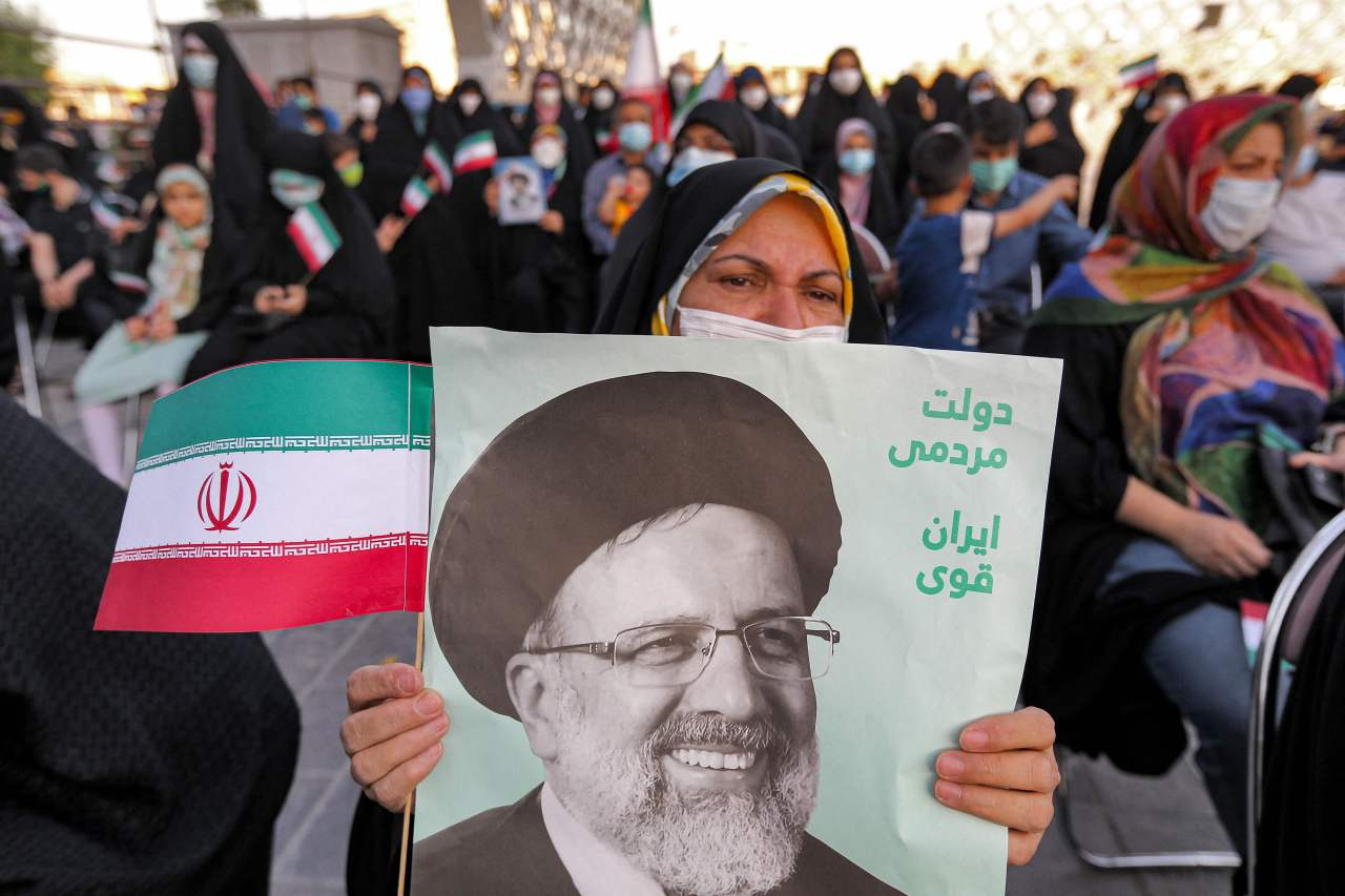 A woman holds a poster of Iran's newly-elected president Ebrahim Raisi, with text in Persian reading