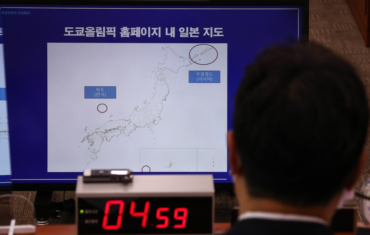 Culture, Sports and Tourism Minister Hwang Hee looks at the map of the route of the Tokyo Olympic torch relay that includes the East Sea islets of Dokdo as Japanese territory during a parliamentary committee's general meeting held at the National Assembly in Seoul on Monday. South Korea has been in effective control of Dokdo since its liberation from Japan's 1910-45 colonial rule. (Yonhap)