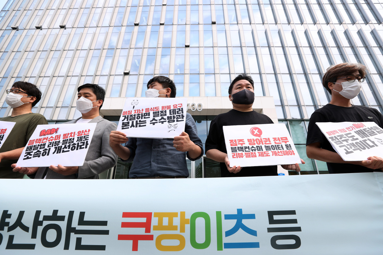 Protestors stagted a protest outside Coupang's headquarters in Seoul on Tuesday over the review system on the company's food delivery app Coupang Eats and its failure to provide protection to restaurant owners.(Yonhap)