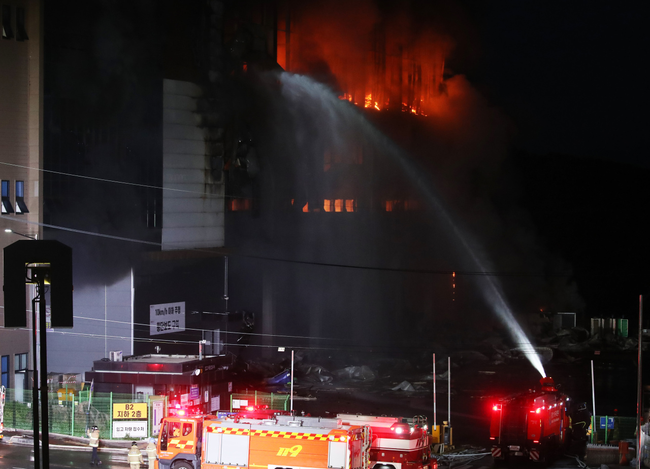 Firefighters try to put out a fire at a Coupang distribution center in Icheon, some 80 kilometers south of Seoul, last Thursday. (Yonhap)