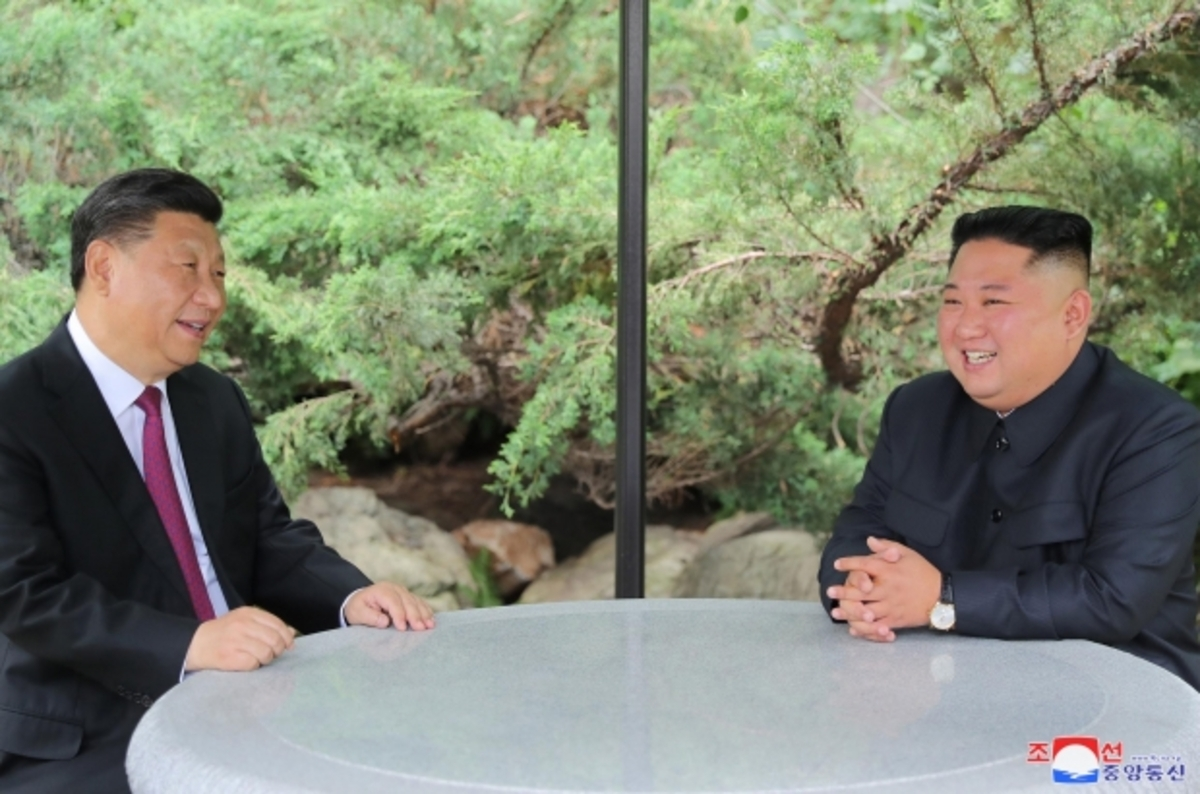 Chinese President Xi Jinping (L) and North Korean leader Kim Jong-un chat at the Kumsusan State Guesthouse in Pyongyang on June 21, 2019, in this photo released by the North's official Korean Central News Agency. (Korean Central News Agency)