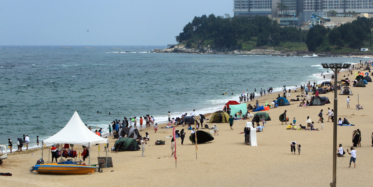 A beach in Sokcho, Gangwon Province, on Sunday is filled with visitors enjoying their day off. (Yonhap)