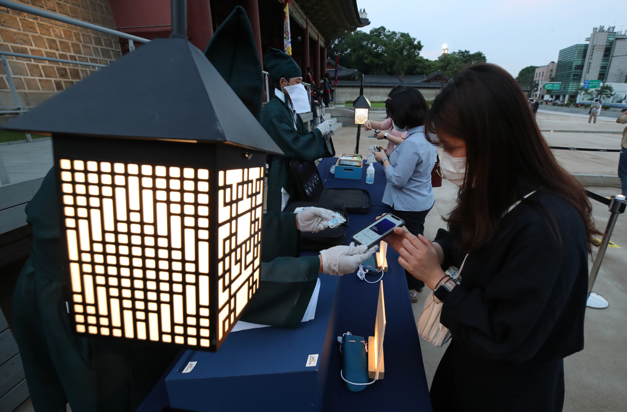 People show their COVID-19 vaccine certificates before entering the Moonlight Tour event at ChangdeokPalace in Seoul on Wednesday. (Yonhap)